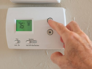 A man's hand adjusting the thermostat to increase the temperature in a home